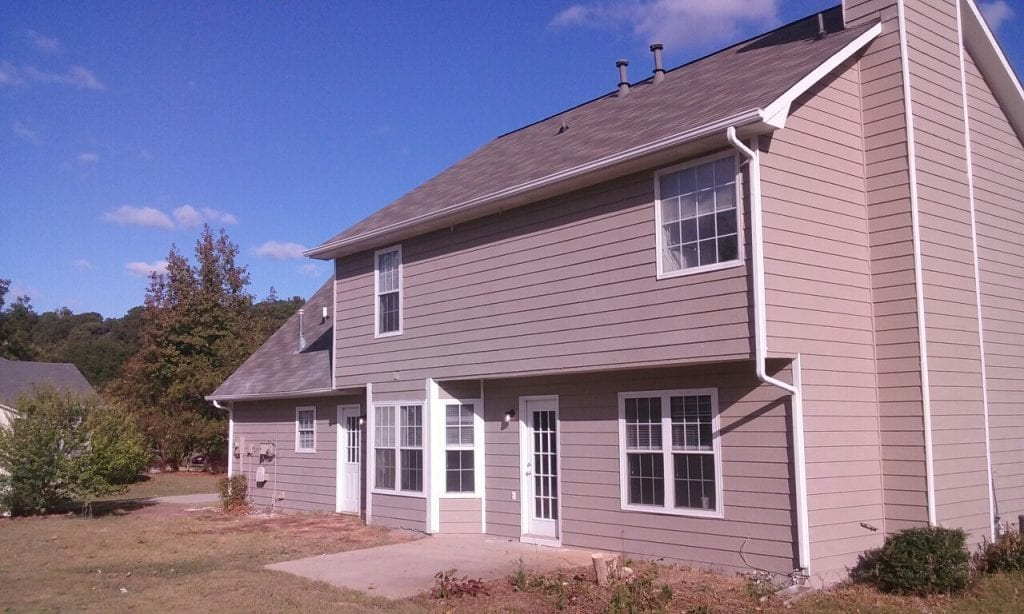 After: an updated exterior with new siding and a new roof