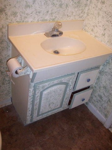 Before: a very outdated bathroom vanity with bad wallpaper